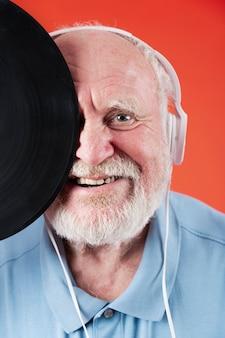 Close-up smiley seniro z nagraniami muzycznymi