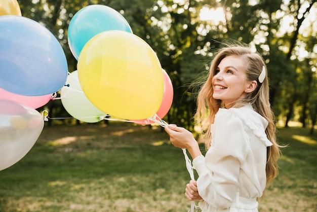 Close-up smiley urodziny dziewczyny z balonami
