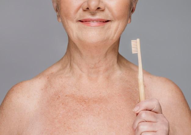 Close-up smiley woman trzymając szczoteczkę do zębów