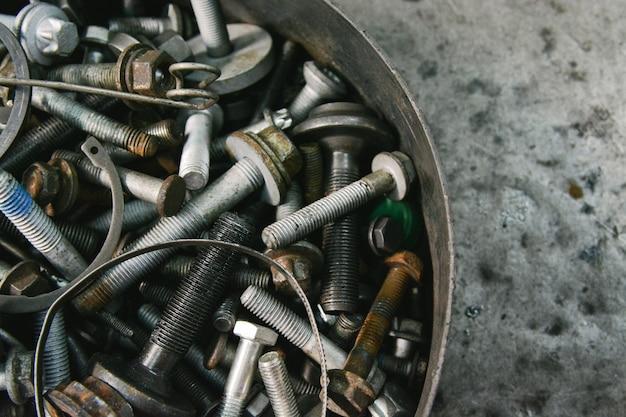Close-up śruby, nakrętki, zapięcie, brutalne metalowe tło z teksturą.