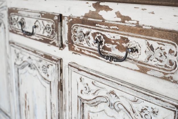Close-up starożytnych białych komódkowych mebli biurowych z farbą odklejoną