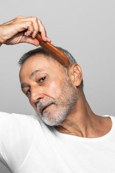 Close-up starszy mężczyzna czesanie włosów