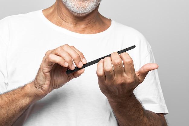 Close-up starszy mężczyzna piłowanie paznokci