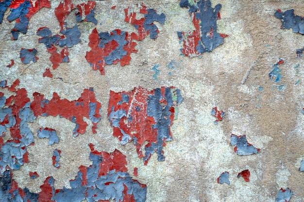 Close-up stary kolorowy betonowy mur. zwietrzała ściana z wyszczerbioną niebiesko-czerwoną farbą. pęknięta tekstura, streszczenie tło.