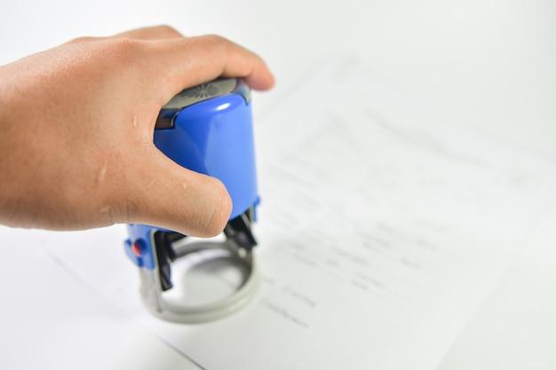 Close-up stemplowanie ręczne na papierze umowy.