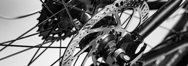 Close-up strzał z nazwanego mechanika hamulca tarcza na rowerze w czerni i bieli
