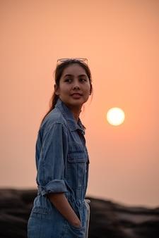Close-up szczęśliwa piękna azjatycka kobieta w okularach stojąc na klifie wieczorem w parku narodowym