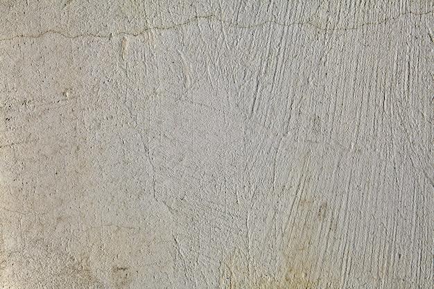 Close-up szorstki, szary tynk betonowy, stary zniszczony, z pęknięciami i zadrapaniami, teksturowana powierzchnia.