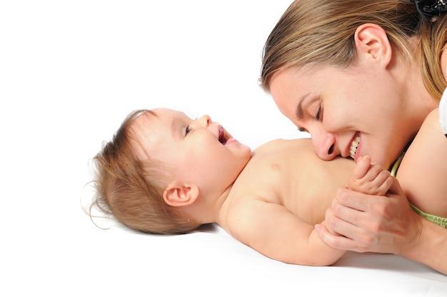 Close-up troskliwa młoda matka bawi się z małą uroczą półroczną dziewczynką po kąpieli na białym tle
