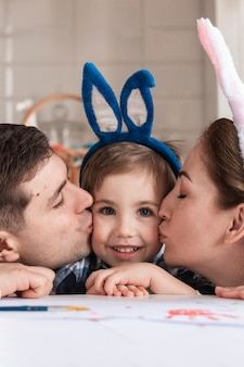 Close-up urocze dziecko jest całowane przez matkę i ojca