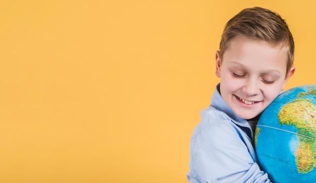 Close-up uśmiechniętego chłopca obejmującego świecie przed żółtym tle