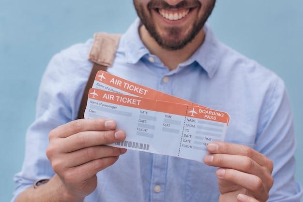 Close-up uśmiechnięty mężczyzna pokazuje bilet lotniczy