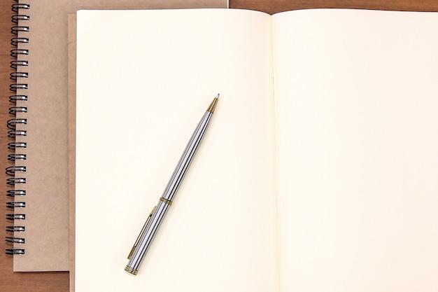 Close-up uwaga książka z piórem na stole.