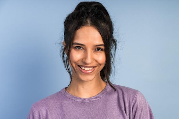Close-up widok atrakcyjnej brunetki pozowanie. dziewczyna szczerze się uśmiecha, patrzy w kamerę