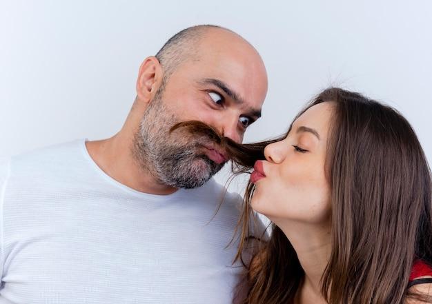 Close-up widok dorosłej pary figlarny mężczyzna czyniąc wąsy z włosów kobiety patrząc na jej kobietę robi gest pocałunku
