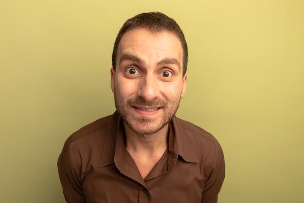 Close-up widok pod wrażeniem młodego człowieka rasy kaukaskiej patrząc na aparat uśmiecha się na białym tle na oliwkowym tle z miejsca na kopię