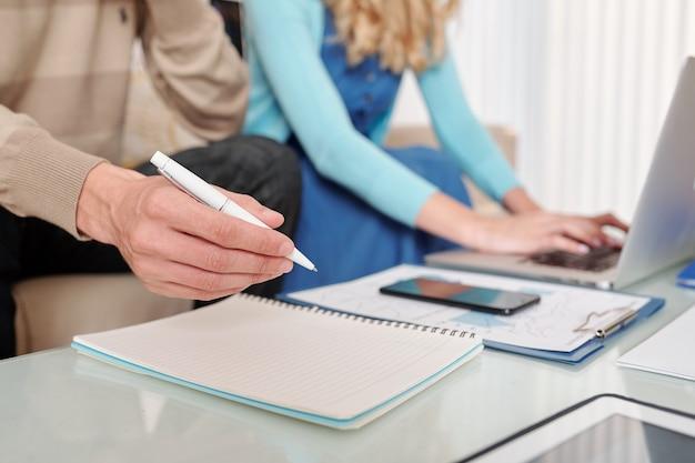 Close-up wizerunek biznesmena analizowania wykresów finansowych i spisywania pomysłów i planów
