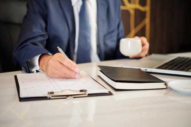 Close-up wizerunek biznesmena o filiżankę kawy podczas analizowania statystyk finansowych w raporcie