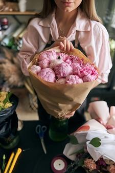 Close-up wizerunek kobiet kwiaciarni, dzięki czemu piękny bukiet świeżych kwiatów.