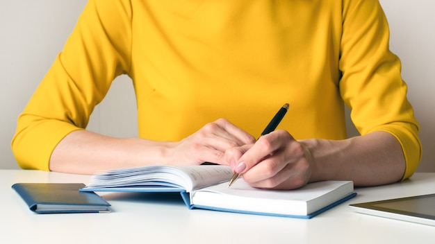 Close-up wizerunek kobiety w żółtej sukience siedzącej przy biurku i pisania czegoś w białym pustym notatniku