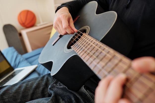 Close-up wizerunek utalentowanego nastoletniego chłopca, grającego na gitarze i śpiewającego w domu