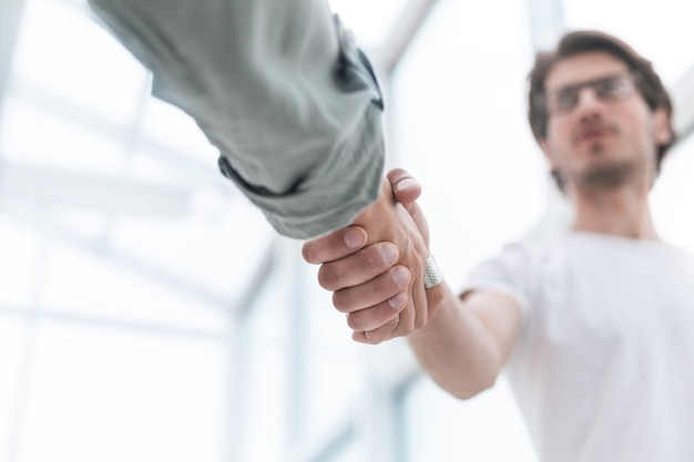 Close up.young man uścisk dłoni ze swoim partnerem biznesowym.koncepcja współpracy