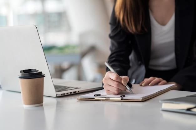 Close-up z businesswoman robienia notatek i korzystania z laptopa w biurze.