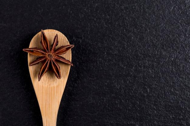 Close-up z drewnianą łyżką z anyżu na czarnym kamieniu. tradycyjna przyprawa