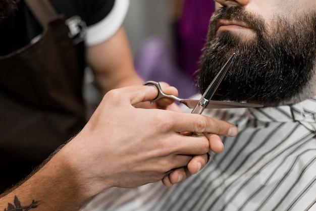 Close-up z fryzjera ręcznego cięcia brody z nożyczkami
