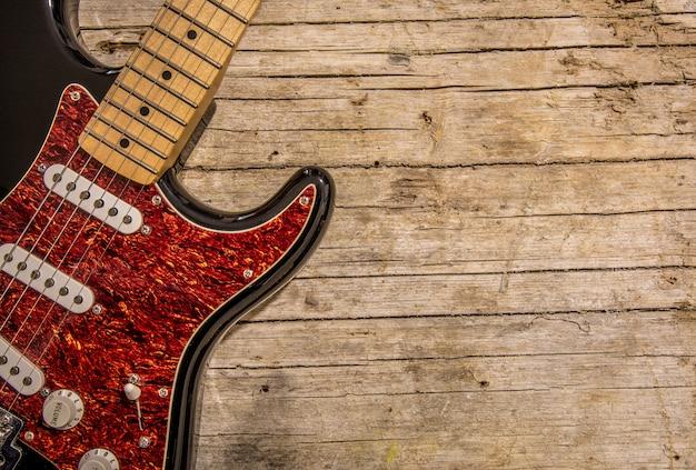Close-up z gitary elektrycznej leżącego na vintage drewna