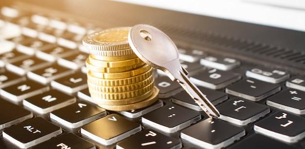 Close-up z klucza i stosu monet na czarnej klawiaturze. pojęcie ubezpieczenia