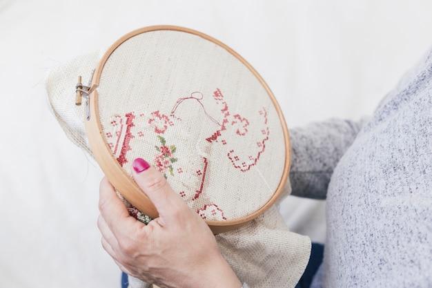 Close-up z kobietą cross stitching na obręczy