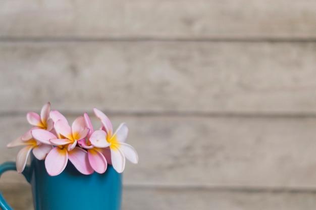 Close-up z kwiatów na niebieskim tle kubek i drewniane