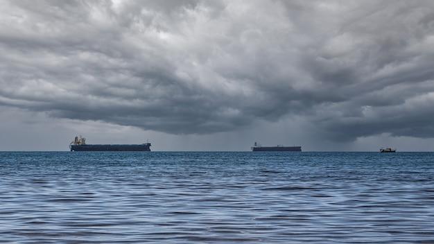 Close-up z mętnym krajobrazem w deszczowy letni dzień. błękitne morze, chmury burzowe nad horyzontem i kilka statków towarowych.