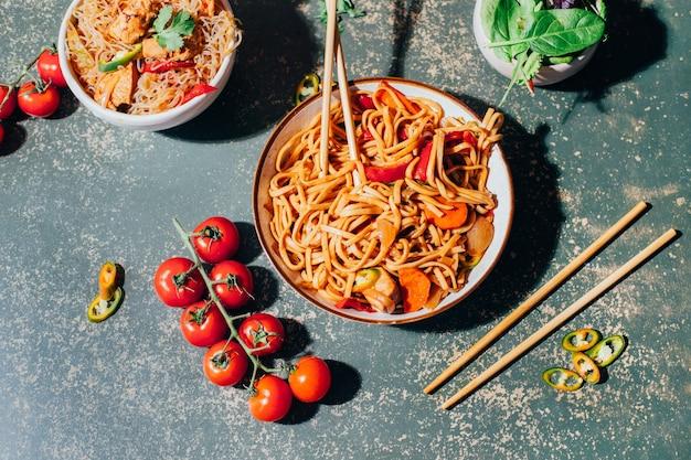 Close-up z naczynia chińskiego makaronu z mięsem i warzywami w talerzach i chińskie pałeczki na zielono