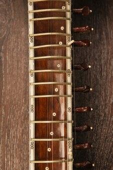 Close-up z podstrunnica sitar indyjski instrument muzyczny leżący na drewnianej podłodze - obraz