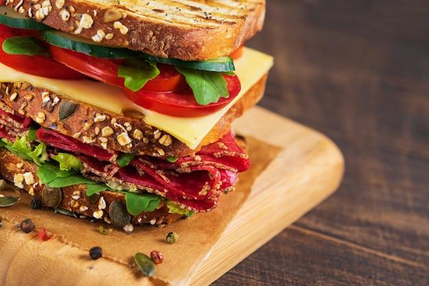 Close-up z pyszną kanapkę z salami, serem i świeżymi warzywami.
