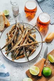 Close-up z sardeli smażonej ryby w talerzu obok piwa w okularach i wapna na pokładzie