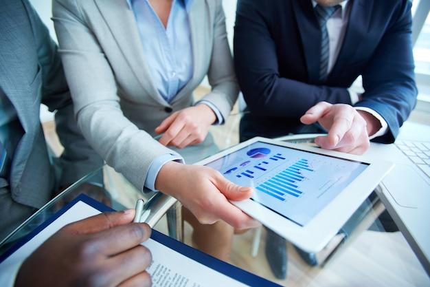 Close-up z touchpadem w ręce wykonawczej w czasie spotkania