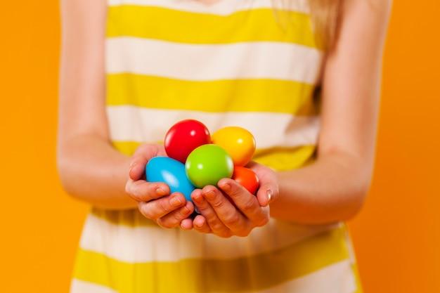 Close-up z wielu kolorowych pisanek w rękach