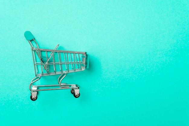 Close-up z wózka na zakupy na zielono z jakimś miejscem na kopię