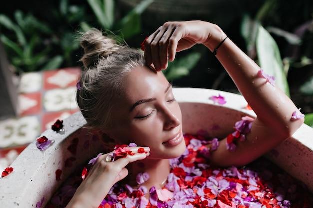 Close-up zdjęcie atrakcyjnej opalonej kobiety chłodzenie w wannie pełnej płatków róż. kryty strzał wyrafinowanej blond modelki korzystającej ze spa z delikatnym uśmiechem.