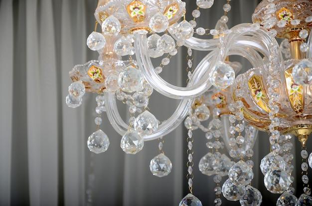 Close-up zdjęcie scenerii na starym żyrandolu. szklane figurki lśnią i odbijają światło swoimi twarzami