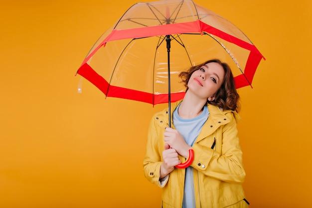 Close-up zdjęcie uroczej białej dziewczyny trzymającej parasol i delikatnie uśmiechając się. wewnątrz portret beztroskiej krótkowłosej modelki w żółtym jesiennym płaszczu.