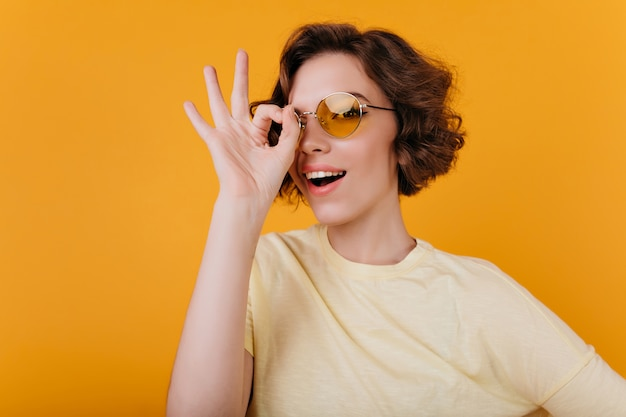Close-up zdjęcie uroczej bladej dziewczyny w żółtych okularach przeciwsłonecznych