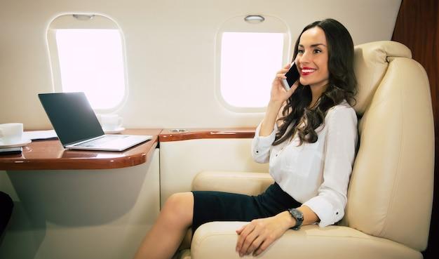 Close-up zdjęcie uroczej kobiety latającej w klasie biznes, która uśmiecha się i patrzy w kamerę podczas rozmowy przez telefon.