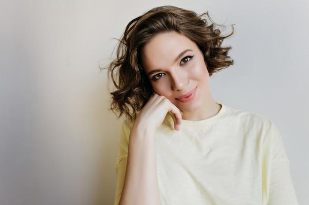 Close-up zdjęcie uroczej młodej damy z romantycznym uśmiechem. wewnątrz portret inspirowanej krótkowłosej dziewczyny o pięknych oczach na białej ścianie.