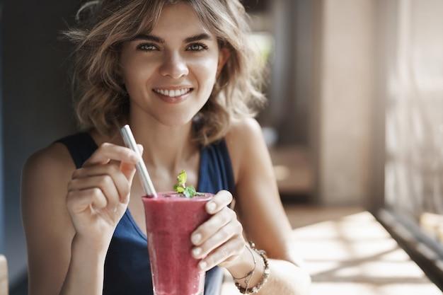 Close-up zdrowy atrakcyjny stylowy europejski blond kręcone włosy uśmiechnięta szeroko siedząca kawiarnia stolik w pobliżu okna trzymać szklaną słomkę napój koktajlowy, diatolog sugeruje dobrze zjeść.