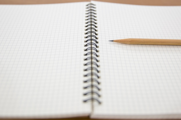 Close-up zeszyt z ołówkiem na stole.