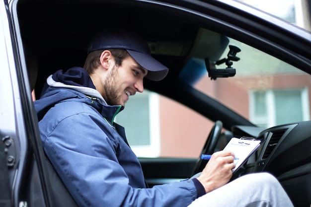 Closeup.man z dokumentami siedzi w samochodzie